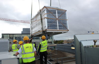 Guiding new supply AHU into place on rooftop